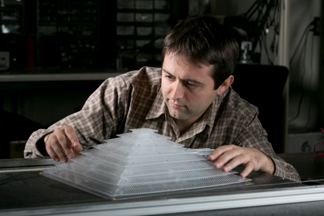 Bogdan Popa, a graduate student in electrical and computer engineering, shows off the 3D acoustic cloak he helped design and build as a member of Steven Cummer's laboratory.